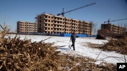 FILE - a Chinese farmer walks past the half completed apartment blocks built to relocate the farmers from Damazizhuang village in northern China's Hebei province. As China tries to protect farmland from development, officials are going after the land underneath farmers' homes instead.