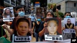 香港示威者在中联办前手举中国维权律师和异议人士的照片抗议国安法。(2020年6月25日)
