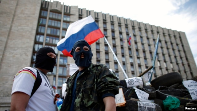 Masked pro-Russia protesters stand guard near a barricade outside a regional government building in Donetsk, in eastern Ukraine, April 23, 2014.