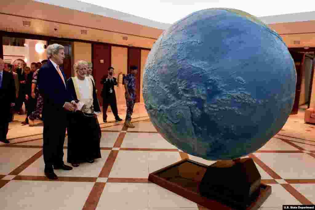 Secretário de Estdo americano, John Kerry, e o Ministro dos Negócios Estrangeiros de Omã, Yusuf bin Alawi, admiram globo terrestre na capital daquele país árabe.