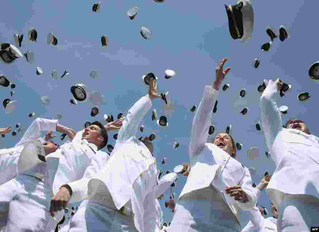 U.S. Naval Academy graduates toss their hats in the air during graduation ceremonies at the U.S. Naval Academy in Annapolis, Maryland.