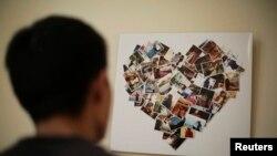 Zhang Zhiliang, warga Tianjin berusia 27 tahun, menatap foto-foto tunangannya Li Jie, penumpang dalam pesawat Malaysia Airlines MH370, di apartemen mereka di Tianjin (5/4).