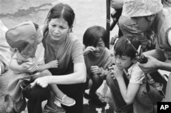 FILE - In this April 29, 1975 file photo, a South Vietnamese mother and her three children are shown on the deck of a ship being taken out of Saigon by U.S. Marine helicopters in Vietnam.