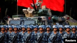 FILE - Troops prepare for the arrival of Chinese President Xi Jinping, June 30, 2017, at the People's Liberation Army Hong Kong Garrison in Hong Kong.