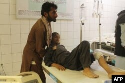 FILE - An Afghan boy is treated at a hospital following an airstrike in Kunduz province, northern Afghanistan, April 2, 2018.