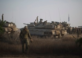 Israeli soldiers work on their tanks at a staging area near the Israel-Gaza Border, Wednesday, July 9, 2014.