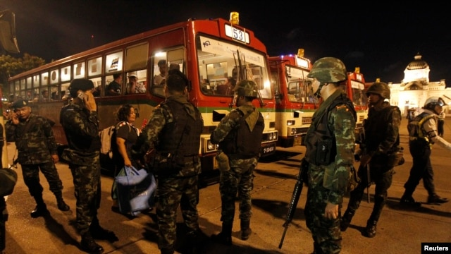 FILE - Thai soldiers stand as anti-government protesters board a bus to head home, at the Royal Plaza in Bangkok.