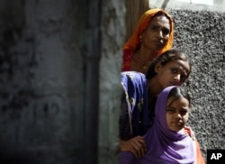 FILE - A woman and two girls peer out from a doorway in a Hindu neighborhood in Lyari, in Karachi, Pakistan, May 5, 2009.