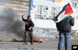 Palestinian demonstrator throws stones during clashes with Israeli troops following protests against U.S. President Donald Trump's decision to recognize Jerusalem as the capital of Israel, in the West Bank city of Ramallah, Feb 2, 2018.