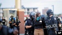 지난달 31일 미국 미네소타주 미니애폴리스에서 경찰들이 야간 통행금지령을 어긴 조지 플로이드 사망 항의 시위대 참가자를 체포하고 있다.