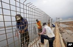 FILE - Workers build a wall that will be used as a barrier to prevent sea water from flowing onto land and cause flooding in Jakarta, Indonesia, Dec. 8, 2015.