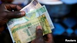A man holds several Gambian banknotes at Serrekunda market in Banjul, Gambia, Jan 27, 2017.