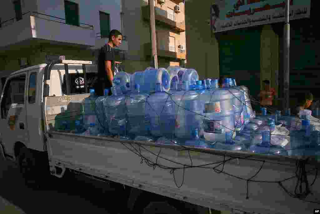 A man sells water from the back of a truck in Tripoli, Libya. Water has been cut off throughout the city, August 26, 2011. (VOA Photo - J. Weeks)