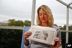 In this Jan. 30, 2019, photo, Mechelle Boyle holds a newspaper with a photo from the school shooting showing her embracing Cathi Rush. (AP Photo/Brynn Anderson)