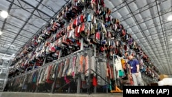 Thousands of clotthes are stored on a three-level system at the ThredUp sorting center in Phoenix on March 12, 2019. (AP Photo/Matt York, File)