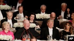 Cardinal Timothy Dolan sits between rival presidential candidates Hillary Clinton, left, and Donald Trump, who's accompanied by wife Melania Trump, at a Catholic charity dinner in New York, Oct. 20, 2016.