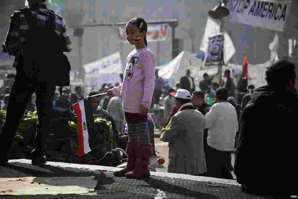 A young girl holds an Egyptian flag in Tahrir Square, November 30, 2012. (Y. Weeks/VOA)