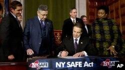 Le gouverneur de New York Andrew Cuomo signe la loi sur le controle d'armes à feu et les munitions à New York et dans le droit lors d'une cérémonie dans la Salle Rouge au Capitole sur le mardi 15 janvier 2013, à Albany, New York