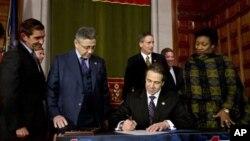 """Gubernur New York, Andrew Cuomo, menandatangani """"NY Safe Act"""" di Albany, New York, 15 Januari 2013. (AP Photo/Mike Groll). New York menjadi negara bagian pertama di Amerika yang memberlakukan aturan untuk memperketat penggunaan senjata api."""