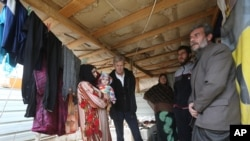 Jan Egeland of the Norwegian Refugee Council, shown second from left as he listens to Syrians at a refugee camp in Marej, Lebanon, told Associated Press that U.N. resolutions seeking to boost humanitarian aid to Syrians have had no effect, Feb. 25, 2015.