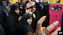FILE - Iranian women demonstrators take a selfie while showing their hands.