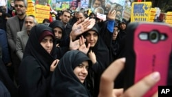 FILE - Iranian women demonstrators take a selfie while showing their hands with slogans against the U.S. and in support of Supreme Leader Ayatollah Ali Khamenei during an annual rally in front of the former U.S. Embassy in Tehran, Iran, Oct. 4, 2015.