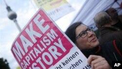 柏林的一位抗议者在工会发动的反对缩减预算的示威中举着标语牌