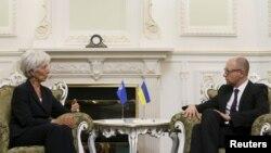 FILE - International Monetary Fund (IMF) Managing Director Christine Lagarde speaks with Ukraine's Prime Minister Arseny Yatseniuk during their meeting in Kiyv, Ukraine, Sept. 6, 2015.