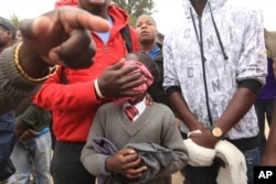 A man covers his daughter's face after she inhailed police teargas.