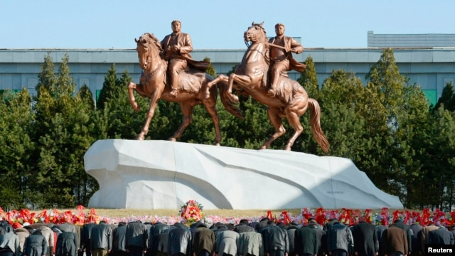 North Koreans bow to bronze statues of North Korea founder Kim Il-sung and late leader Kim Jong-il. (REUTERS/Kyodo)