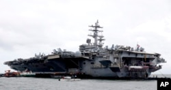 FILE- The U.S. aircraft carrier USS Ronald Reagan is seen anchored off Manila Bay, Philippines, Aug. 7, 2019, for a port call after sailing through the disputed South China Sea amid new territorial flare-ups involving China and rival claimant states.