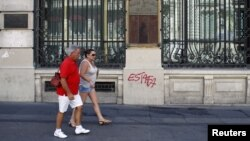 Tourists walk past Spain's former Banco Espanol de Credito in Madrid, August 28, 2012.