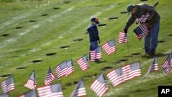 Joseph Manning, right, of Raynham, Mass., and his son Joey, 6, a Cub Scout, place U.S. flags at the graves of deceased veterans at the National Cemetery in Bourne, Mass., Saturday, Nov. 10, 2012.