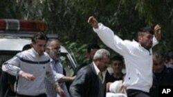 부상자를 안고 시리아-레바논 국경을 넘는 시민들
