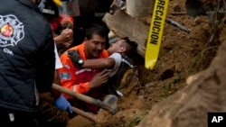 A fireman is rescued after he was trapped while working at the site of a landslide in Cambray, a neighborhood in the suburb of Santa Catarina Pinula, about 15 kilometers east of Guatemala City, Oct. 3, 2015.