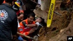2015年10月3日一名消防员在危地马拉山体滑坡的地点工作时被困住后被救出。