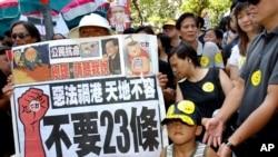 """資料照:香港民眾舉著反對""""惡法""""的標語準備參加反對23條立法的大遊行(美聯社2003年7月1日)"""