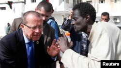 Le représentant spécial de l'U.N. et Chef de la Mission d'appui des Nations Unies en Libye, Martin Kobler écoute un migrant africain lors d'une visite dans un camp de détention à Tripoli, en Libye, le 21 février 2017.