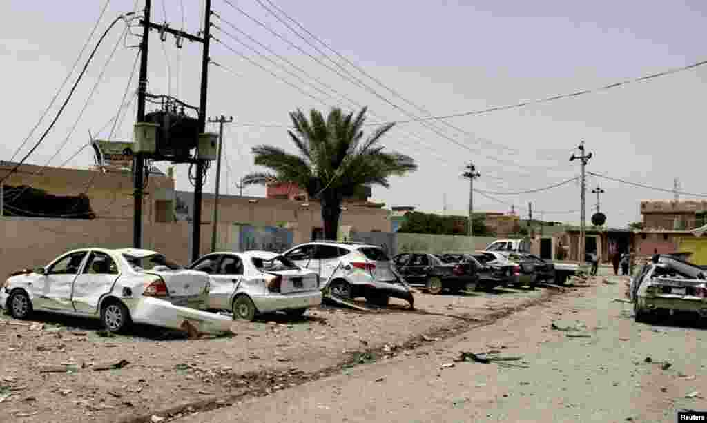 Cars are damaged at the site of a car bomb attack in the town of Jalawla, Iraq, June 8, 2014.