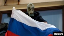 A pro-Russia rebel wearing a gas mask places a Russian flag on the balcony of the city hall in Mariupol, eastern Ukraine May 7, 2014.