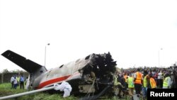 Rescue workers stand near the tail of a plane at the site of a plane crash near the Lagos airport.