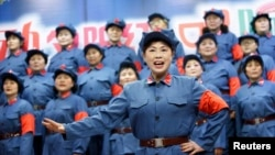 FILE - Retired female workers dressed as red army soldiers sing revolutionary songs.
