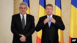 FILE - Romanian President Klaus Iohannis (right) poses with Romanian Prime Minister Mihai Tudose at the Cotroceni Presidential Palace, Bucharest, Romania, June 29, 2017.
