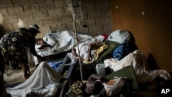 People suffering cholera symptoms rest on stretchers as they crowd the entrance of a public hospital in Limbe village near Cap-Haïtien, Haiti, 22 Nov 2010