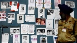 An Indian paramilitary soldier looks at the gate of an airport, covered with special announcements and pictures of missing people, in Jollygrant, India, June 26, 2013.
