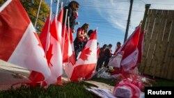 지난 22일 캐나다 오타와 총기 사건으로 사망한 경비병 네이튼 시릴로의 집에서 24일 시릴로의 아들이 다니는 학교 교직원들이 유가족에게 애도를 표하고 있다.