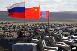 """FILE - Russian, Chinese and Mongolian national flags set on armored vehicles develop in the wind during a military exercises on training ground """"Tsugol, south-east of the city of Chita during the military exercises Vostok 2018 in Eastern Siberia, Russia,"""