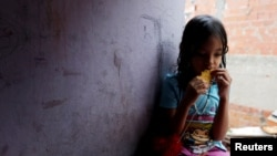 FILE - One of Yennifer Padron and Victor Cordova's daughters eats an arepa in the family room of the house that they share at Petare slum in Caracas, Venezuela, Aug. 21, 2017.