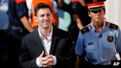 FILE - Argentine soccer star Lionel Messi (L) arrives at a court to answer questions in a tax fraud case in Gava, near Barcelona, Spain, Sept. 27, 2013.