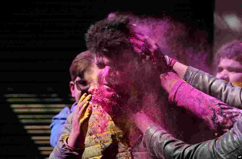 Indians put colored powder on each other as they celebrate Holi in Jammu.